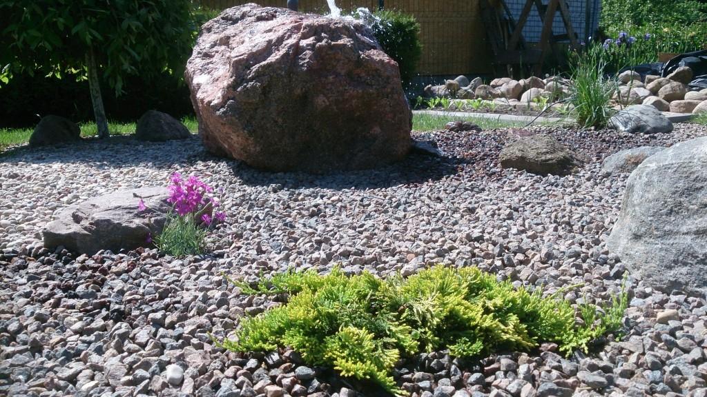 Fontanas iš akmens ir minimali augalų kompozicija.